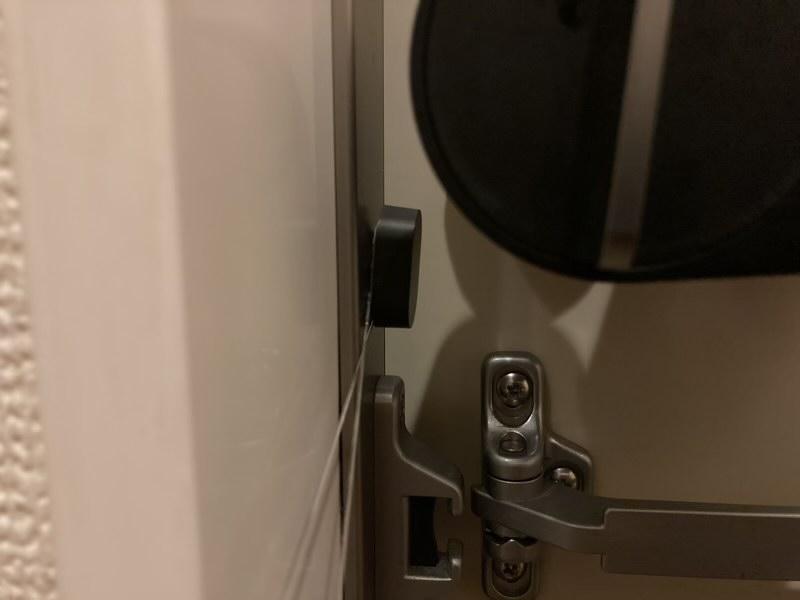 糸で少しづつQrio Lockの開閉センサーを剥がします